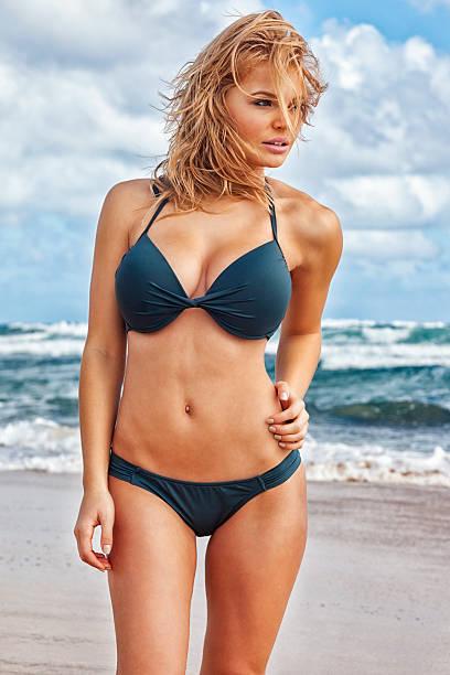 sexy young blonde woman wearing green bikini on hawaiian beach - busty women in bikinis stock pictures, royalty-free photos & images