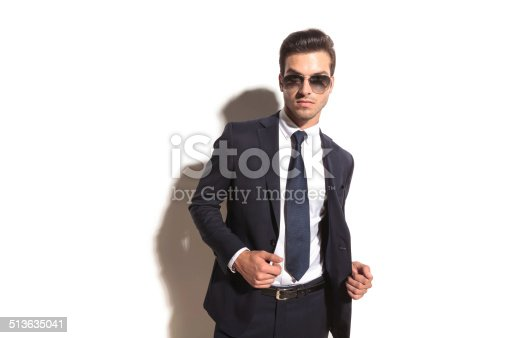 907934274 istock photo sexy young business man with sunglasses opening his coat 513635041