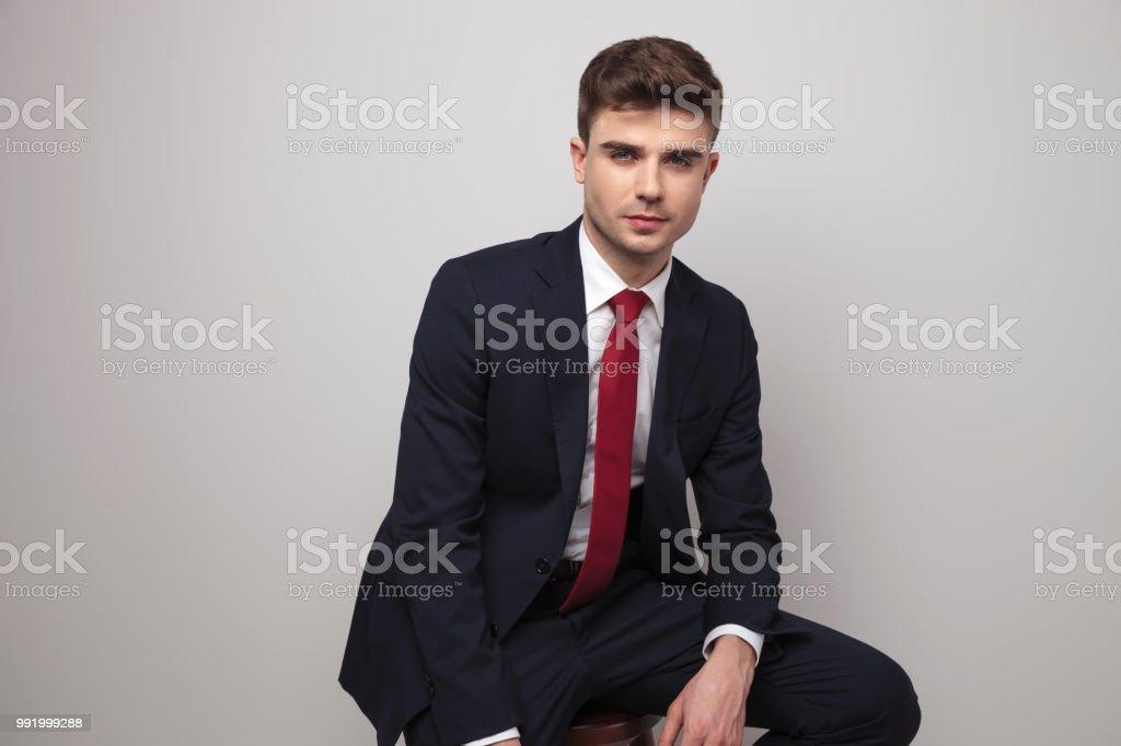 68447215e3f84 sexy jeune homme d'affaires en costume marine est assis sur le tabouret en  bois