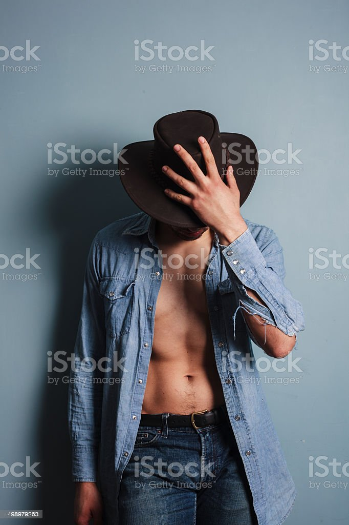 Sexy young cowboy with his shirt open stock photo