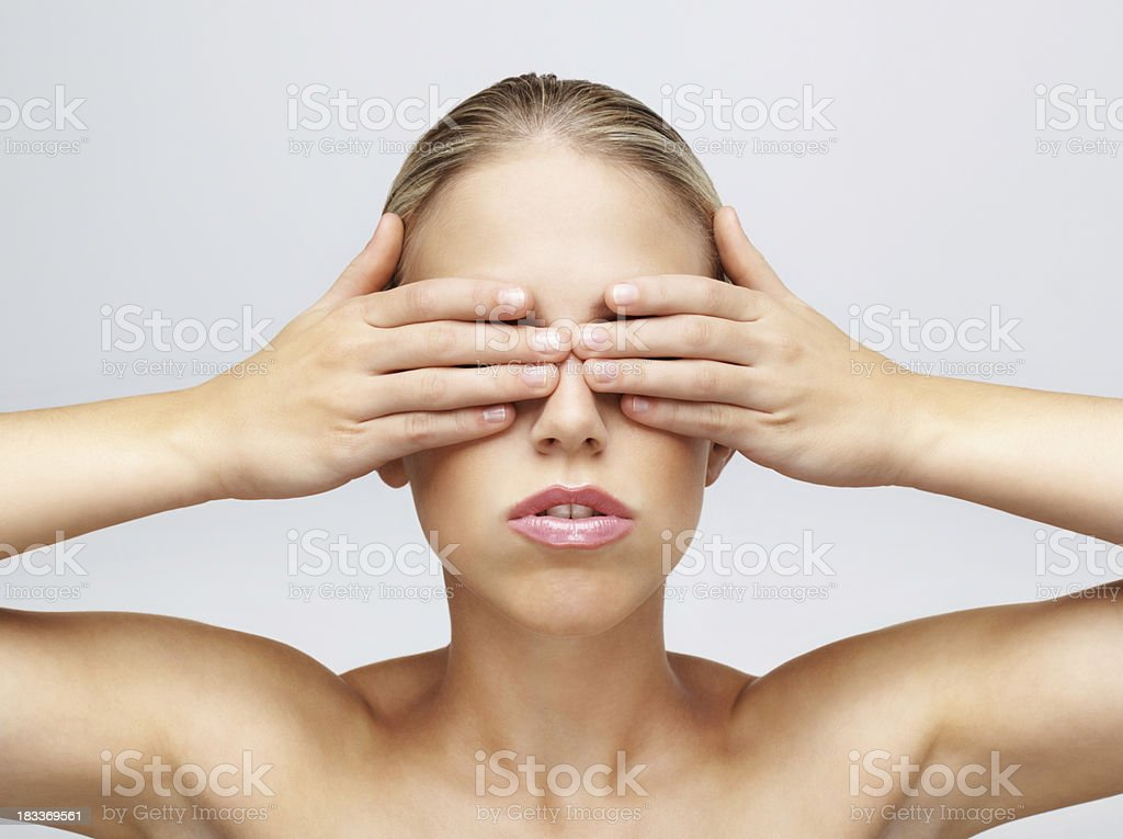 Sexy young female covering her eyes against white background royalty-free stock photo