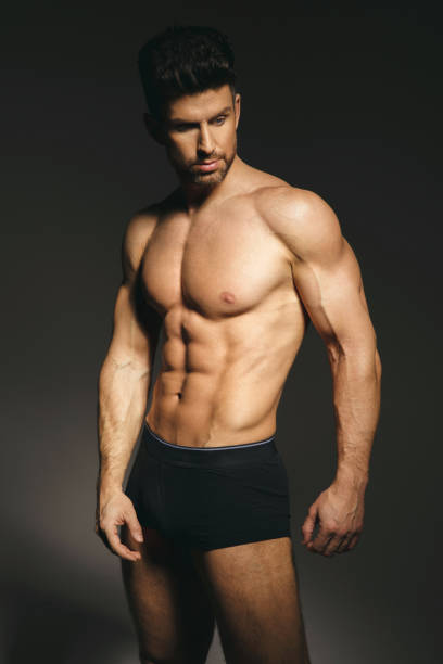 Sexy young male model with muscular chest and six pack posing in studio, young sexy bodybuilder Fitness model posing in underwear shirtless male models stock pictures, royalty-free photos & images