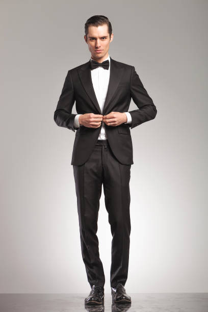 sexy young man in tuxedo and bowtie buttoning his suit - tuxedo stock photos and pictures