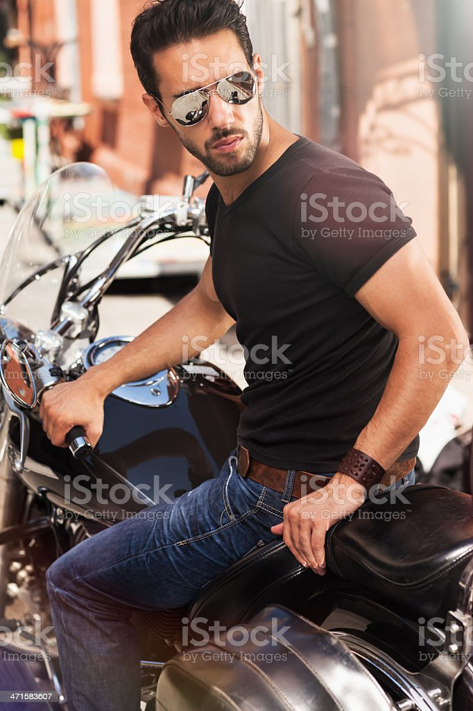 Sexy young man sitting on motorbike royalty-free stock photo