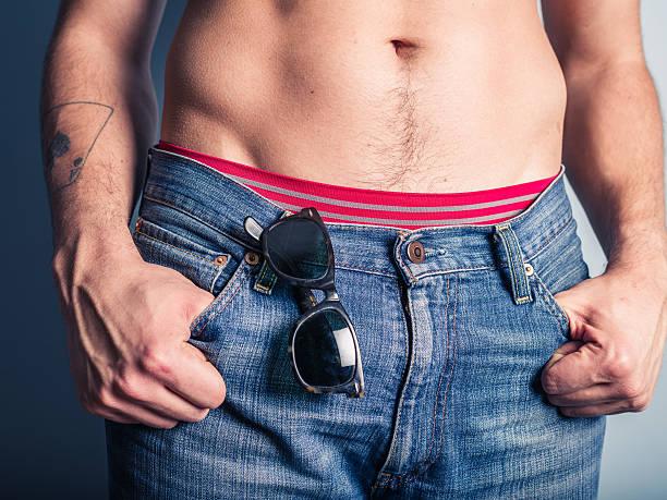 sexy junger mann mit sonnenbrille in seiner tasche - hipster unterwäsche stock-fotos und bilder