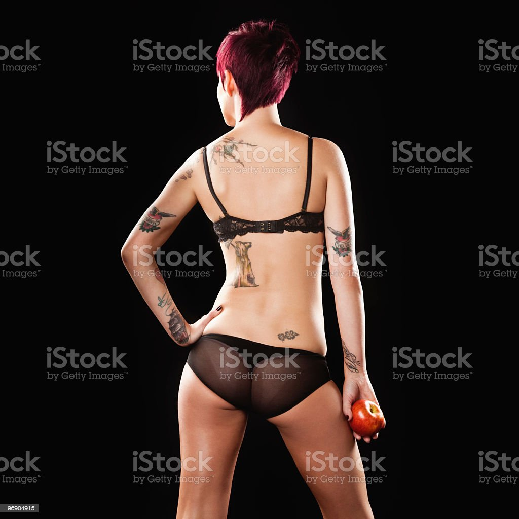 Sexy Young Tattooed Woman Holding Apple royalty-free stock photo