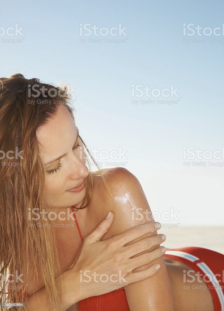 Sexy young woman applying sunblock on her hand royalty-free stock photo