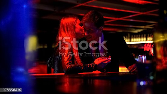 istock Sexy young woman drinking beverage and flirting with man in nightclub party 1072206740