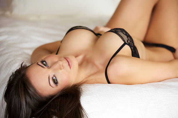Sexy Young Woman in Lingerie on a Bed stock photo