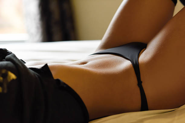 sexy young woman in lingerie posing on the bed - underwear stock photos and pictures
