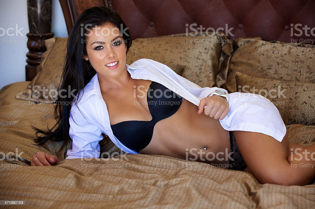 Sexy Young Woman Laying on a bed stock photo