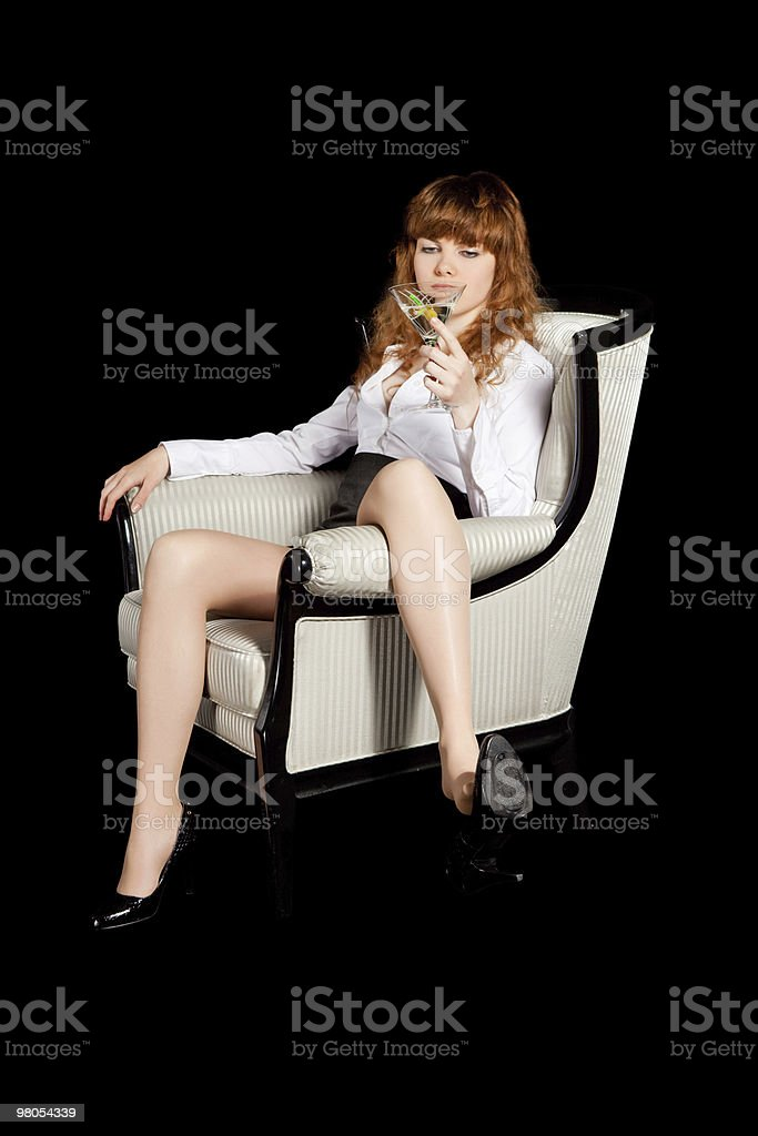 sexy giovane donna in poltrona con un bicchiere di cocktail foto stock royalty-free
