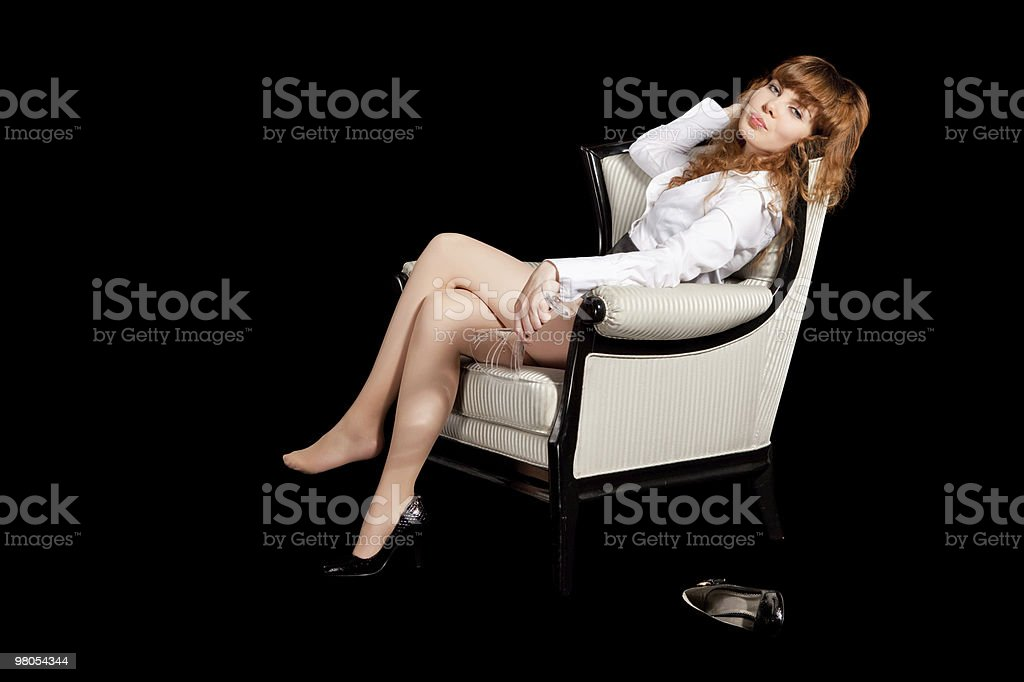 sexy giovane donna in poltrona con un bicchiere di cocktail foto stock royalty-free