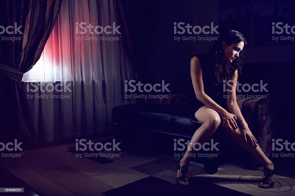 Sexy young woman sitting alone in bedroom stock photo