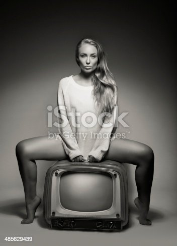 istock Sexy young woman sitting on a TV 485629439