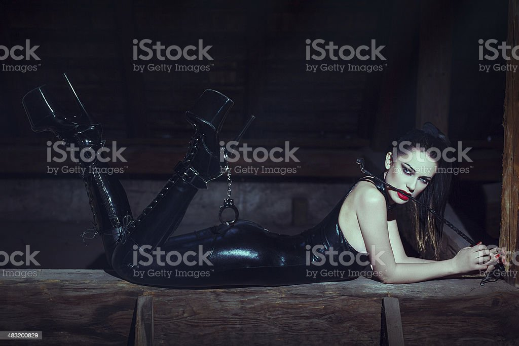 Sexy young woman with whip in mouth stock photo