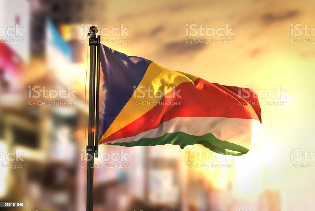 Seychelles Flag Against City Blurred Background At Sunrise Backlight stock photo