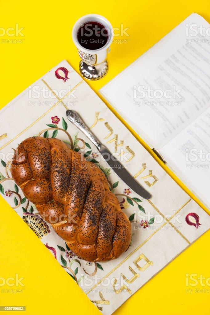 Shabbat, challah on napkin with Kiddush, book on yellow background. stock photo