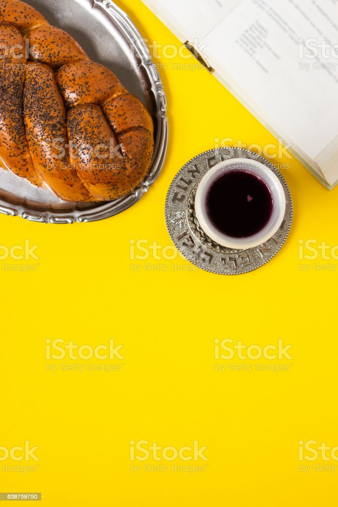 Shabbat, challah on tray, with Kiddush, book on yellow background. stock photo