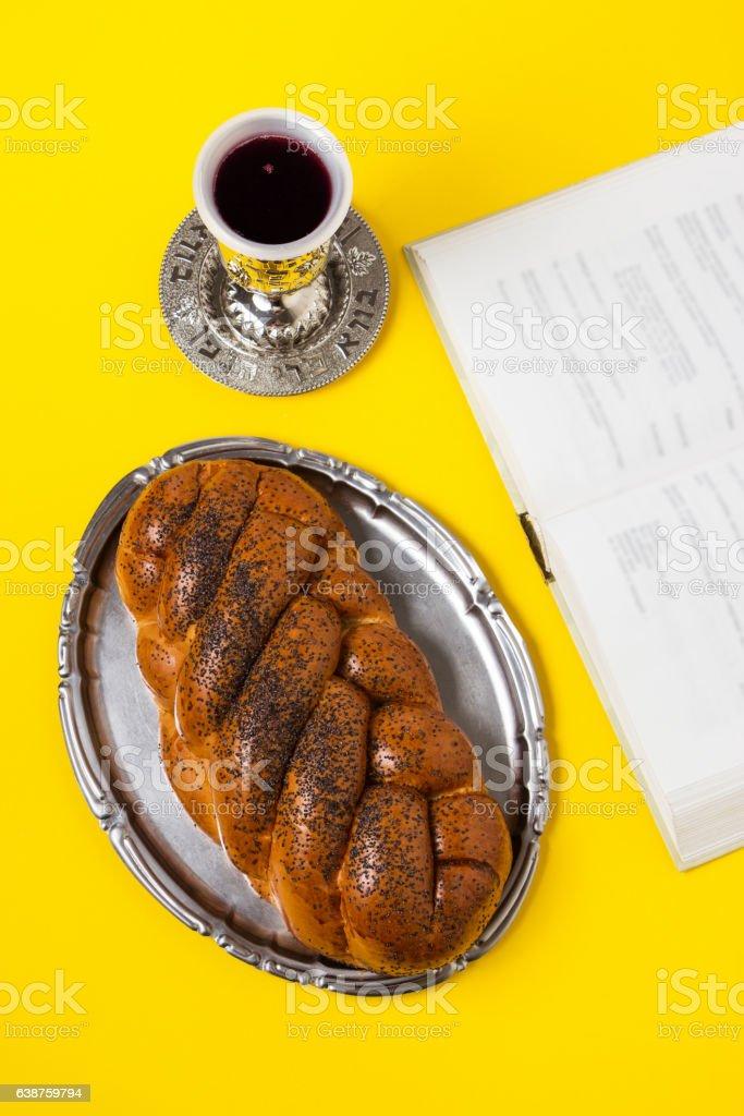 Shabbat, challah on tray, with Kiddush, book on yellow background. stock photo