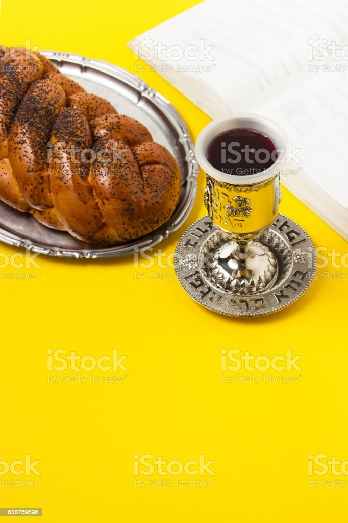 Shabbat, challah with glass of wine, book, on yellow background. stock photo