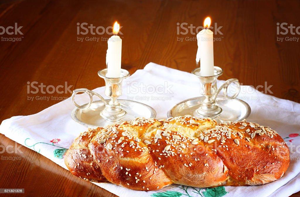 shabbat image. challah bread, shabbat wine and candelas on woode stock photo