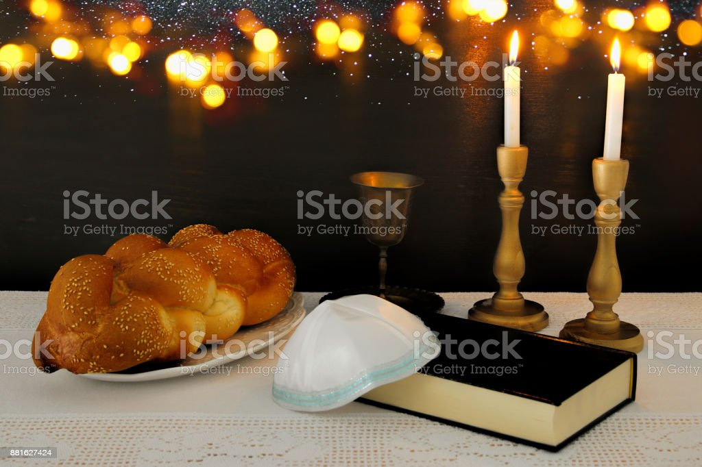 shabbat image. challah bread, shabbat wine and candles on the table. stock photo