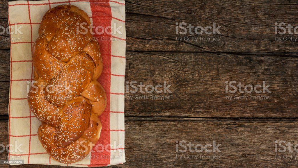 Shabbat or Sabbath kiddush ceremony composition with a traditional sweet fresh loaf of challah bread on a vintage wood background with copy space stock photo