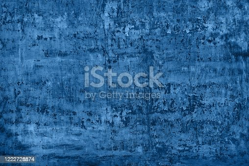 shabby blue stucco with cracks and flakes of paint