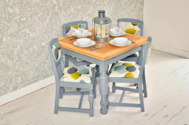 shabby chic dining table with chairs and tableware stock photo