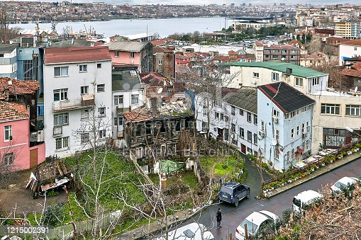 Istanbul, Turkey - February 12, 2020: Decaying housing in the Beyoglu area, and a view of the Golden Horn Bay with the old town on the opposite bank.