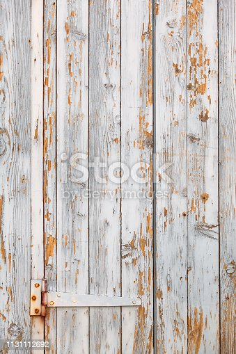 Shabby chic white wooden plank door with rusty hinge and flaking paint (copy space)