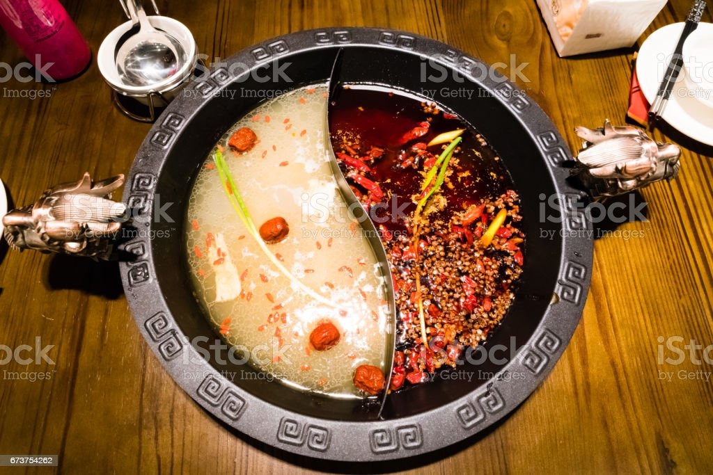 Shabu pot in Chinese style - pork soup and oily spicy soup stock photo