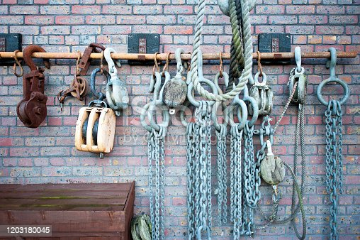 Shackles, chains and pulley blocks hanging on a wall, Bristol docks quayside, Bristol, England. Bristol's historic dockyard has been the centre for the shipbuilding, industry, slave trade, manufacturing, and import/export of produce globally - an important trading, city in the west of England, UK,