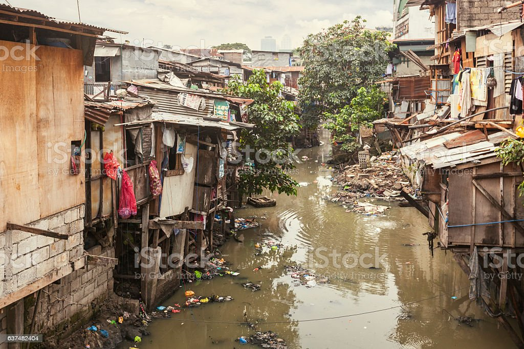 Shacks along a polluted canal Shacks in a slum area along a small polluted canal. Manila, Philippines. Asia Stock Photo