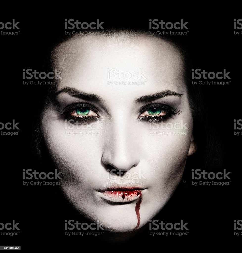 Shaded portrait of a white faced female vampire with blood stock photo