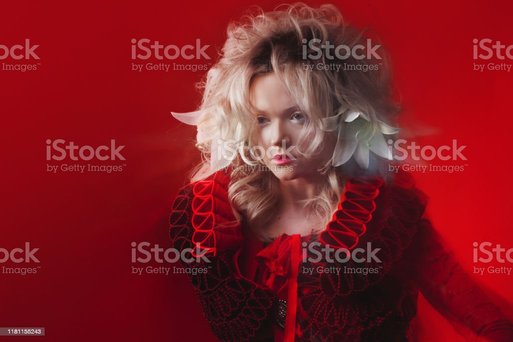 Shades Of Red Portrait Of Bizar Attractive Woman With Fashion Makeup In Fantasy Outfit Posing On A Red Background Stock Photo Download Image Now Istock