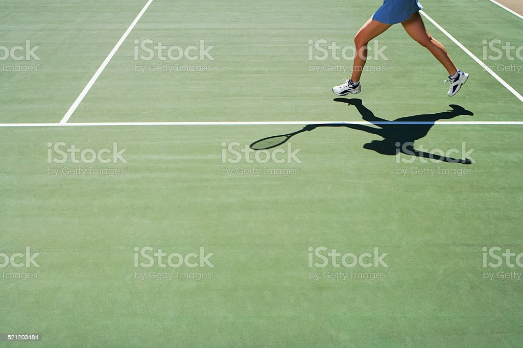 Shadow and legs of person playing tennis stock photo