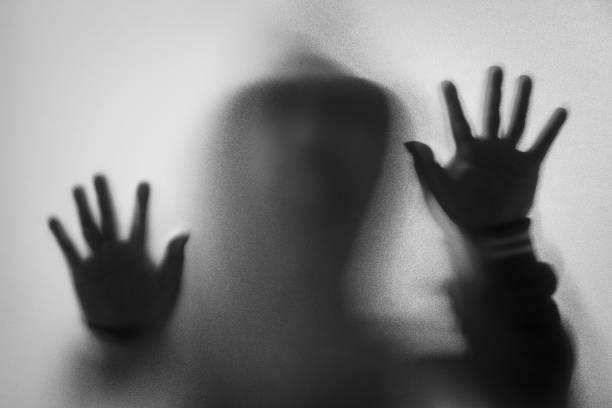 Schatten weichzeichnen des grauen Mannes in Jacke mit Kapuze. Hände auf dem Glas. Gefährlicher Mann hinter Milchglas. Mysterium Mann. Halloween-Hintergrund. Schwarz / Weiß Bild. Bild unscharf – Foto