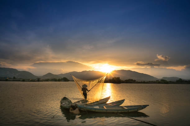 Shadow fishermen at river in the sunset. stock photo