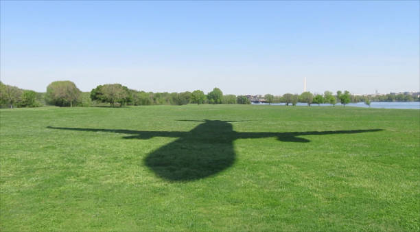 Shadow Jet Photo of the shadow of a jet plane flying low over a grassy field with the Washington Monument and the Potomac River in the background. The picture was taken in Arlington, Virginia, at the Gravelly Point Park, adjacent to Ronald Reagan Washington National Airport. ronald reagan washington national airport stock pictures, royalty-free photos & images