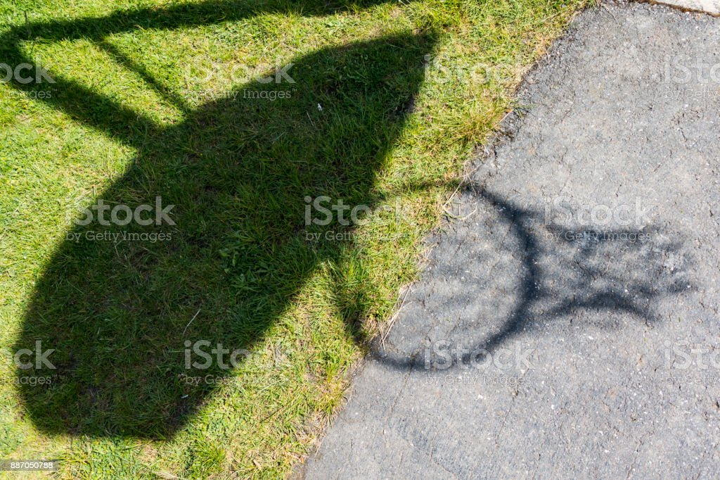 Shadow of a Basketball Hoop Outdoors Over Grass and Concrete stock photo
