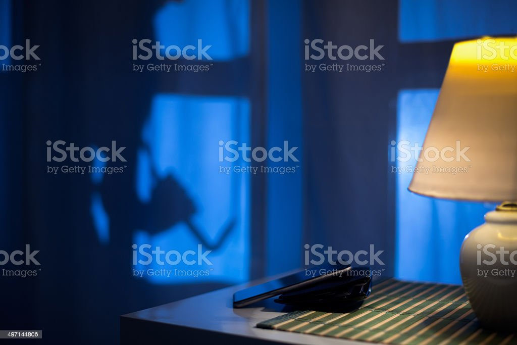 shadow of a burglar sneaking to backdoor at night stock photo