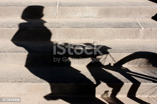812812808istockphoto Shadow of a cyclist pushing his bike up the stairs 872849308