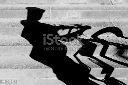 812812808istockphoto Shadow of a cyclist pushing his bike up the stairs 961008924