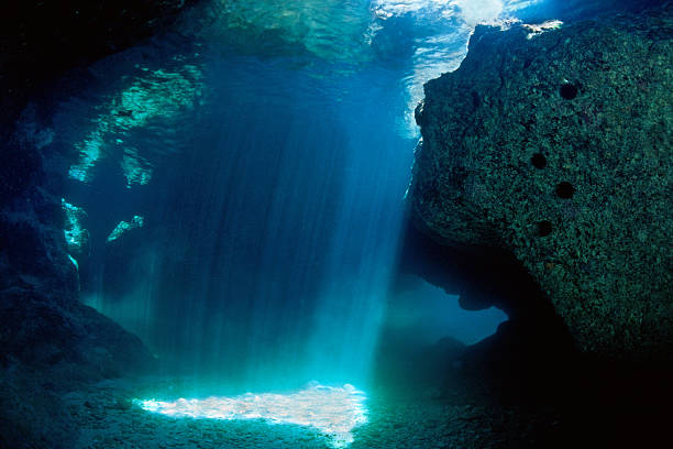 shadow of a grotto subacquea with blue lighting - ocean floor stock photos and pictures