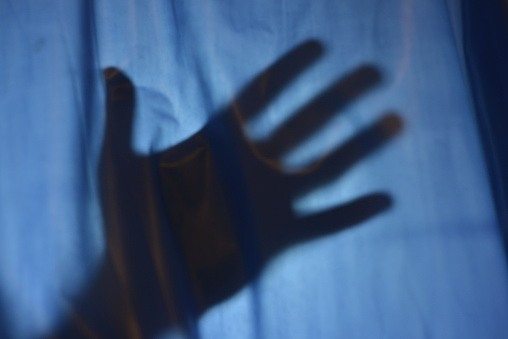istock A shadow of a hand on a dark shower curtain 466764669