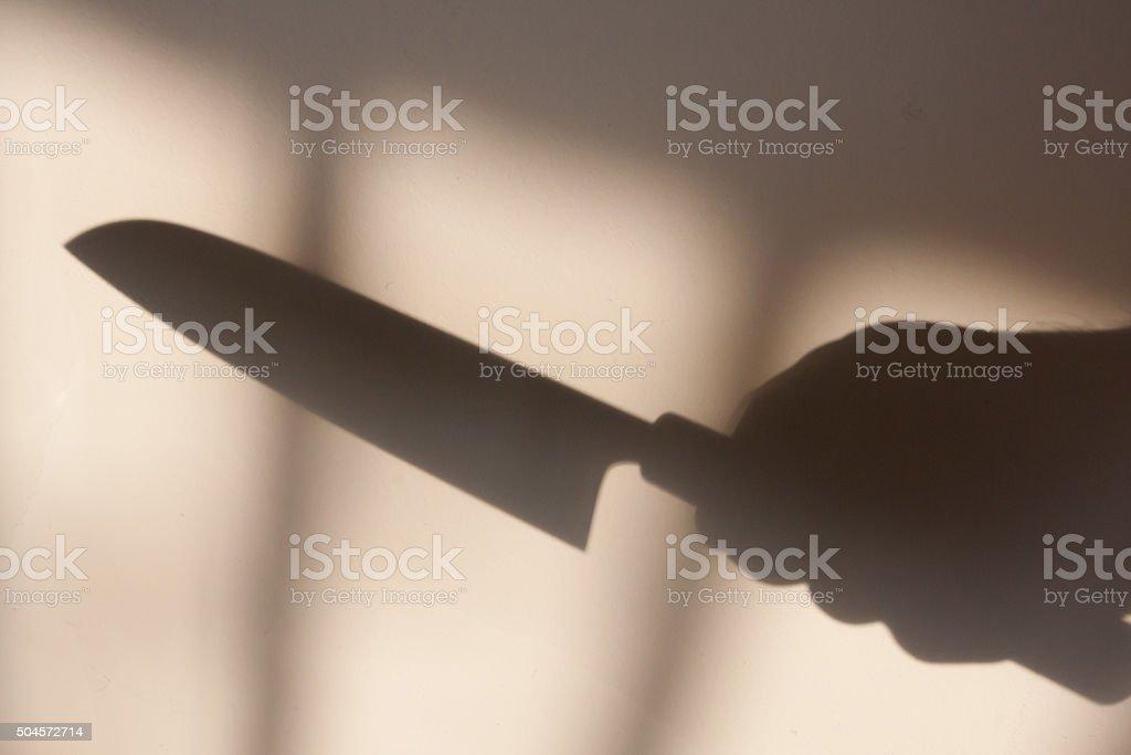 Sombra de uma mão com uma faca. - foto de acervo