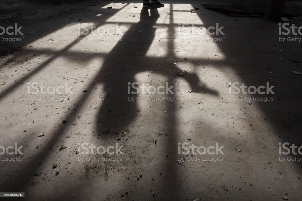 Shadow of a man holding gun in his hand inside of some dark, spooky buiding stock photo