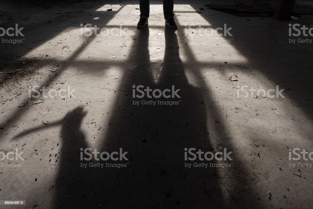 Shadow of a man holding large knife in his hand inside of some dark, spooky buiding stock photo
